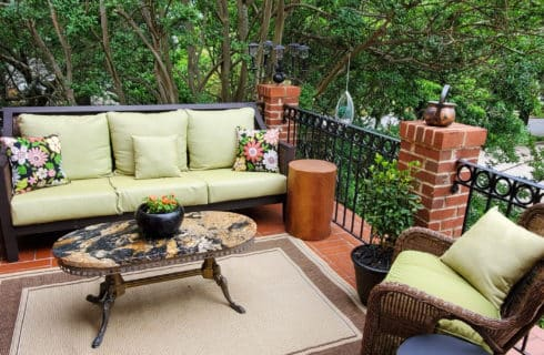 Large green upholstered couch on second floor balcony with marble table.