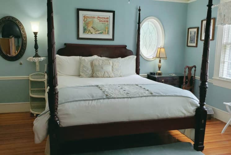 Four poster bed near antique desk and window.