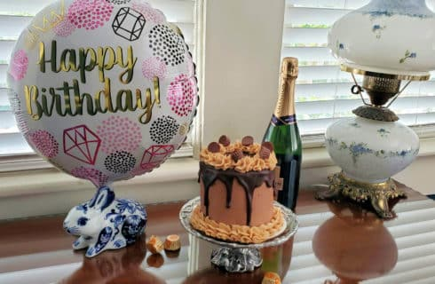 Small Reese's chocolate peanut butter cake with happy birthday balloon and champagne on a wooden desk with lamp and candy in front of window.