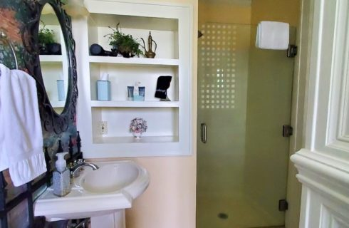 Porcelain sink, three in wall shelves, and shower stall.