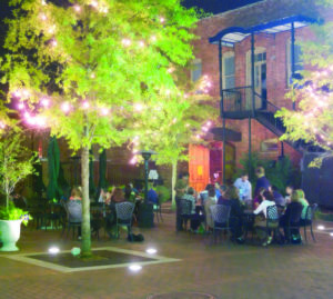 Patio dining at night under twinkle light trees.