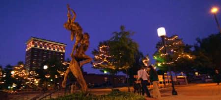 Stone statue on main street at night