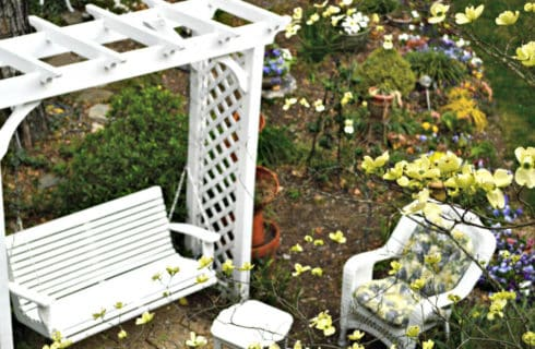 Pretty garden seating area with a white arbor swing and wicker furniture.