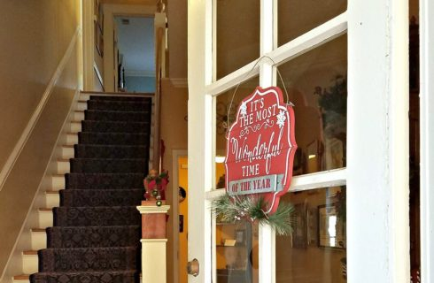 Open French door with red Christmas sign showing a tall carpeted staircase leading to the upstairs of a home