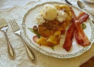 French toast with two pieces of bacon with candied pecans and ice cream on fine china.