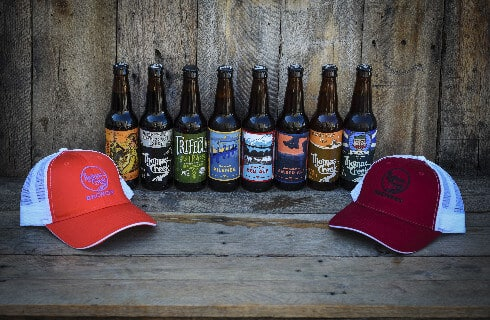 Two ballcaps on a wooden bench in front of a line of 8 different beer bottles.