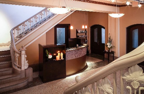 Elegant lobby with grand staircases on either side and an art deco-style front desk.