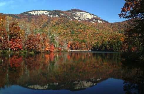 Beautiful view of tall mountain fronted by atumn foliage and a placid lake.