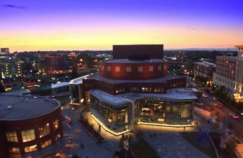 City skyline at dusk featuring a modern theater building in Greenville, NC.