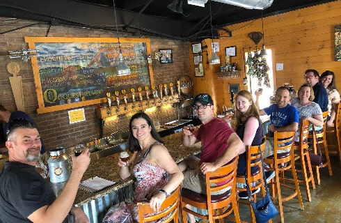Group of smiling people toasting with beer glasses ar a rustic bar.