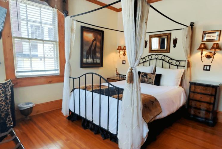 Queen bed on hardwood floor with large flat screen TV.