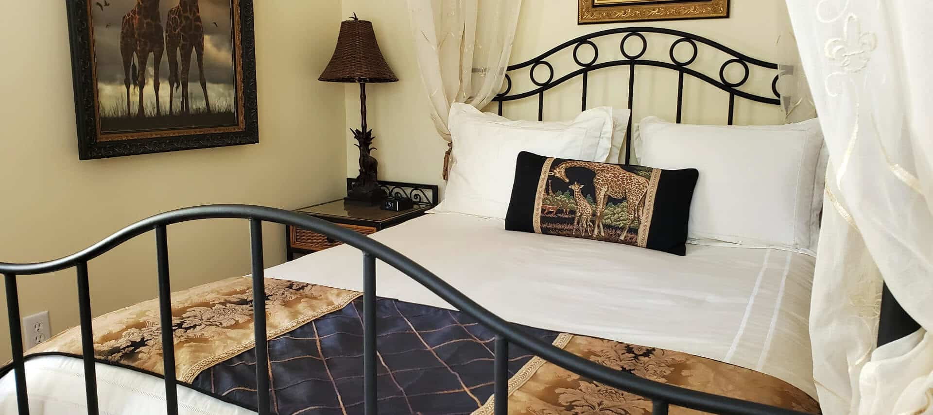 Wrought iron curtained queen bed near night stand with lamp