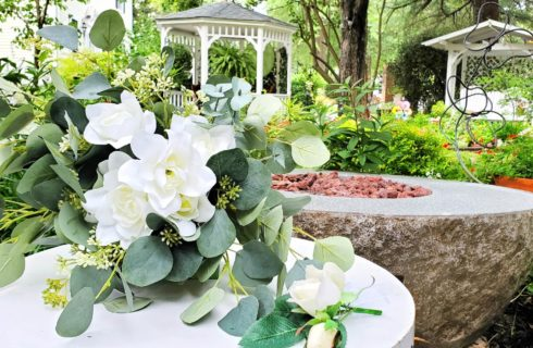 Wedding bouquet in front of gazebo and gardens.
