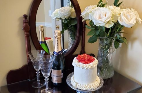 Strawberry and buttercream champagne cake with white roses, champagne, and cut glass flutes on mirrored desk.