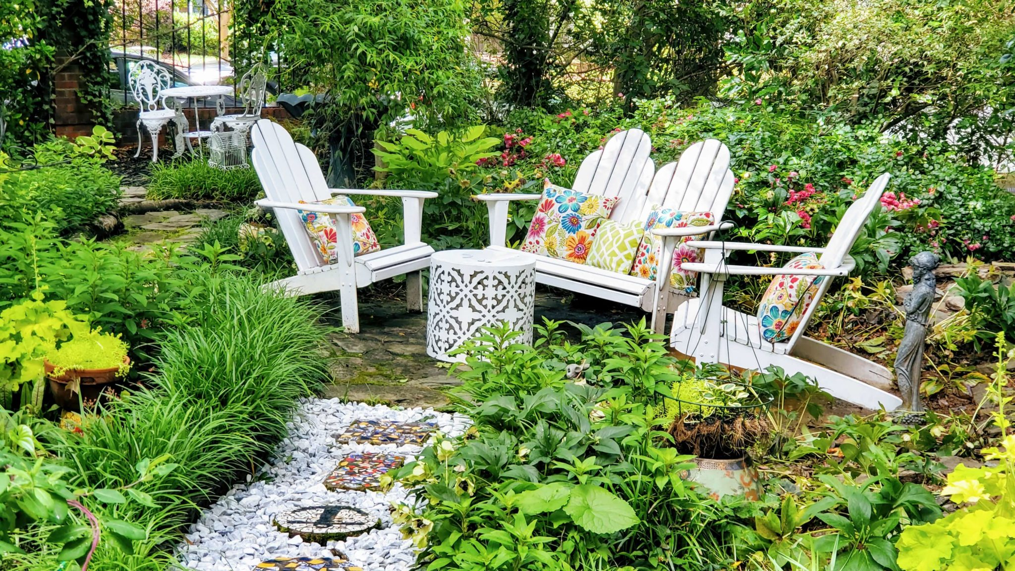 Adirondack chairs in english garden with chipped marble stone pathway.