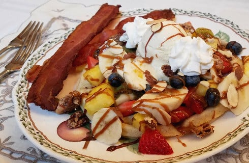 French toast covered with bananas, strawberries, pineapple, blueberries, and whipped cream. accompanied by bacon.