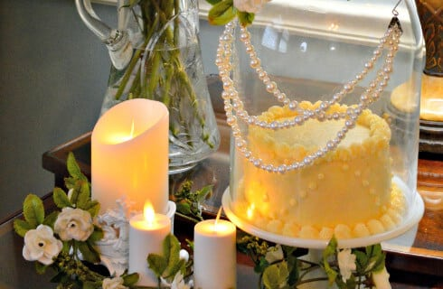Exquisitely decorated small cake under dome decorated with pearls and surrounded with lit white candles.