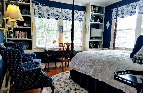Bedroom decorated in dark blue and white with a four-post bed and blue wingback chair.
