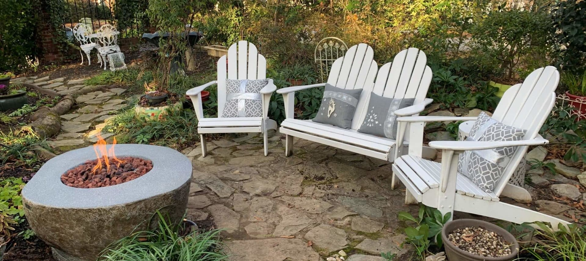 White Adirondack chairs with gray cushions surrounding stone fire table in English garden.
