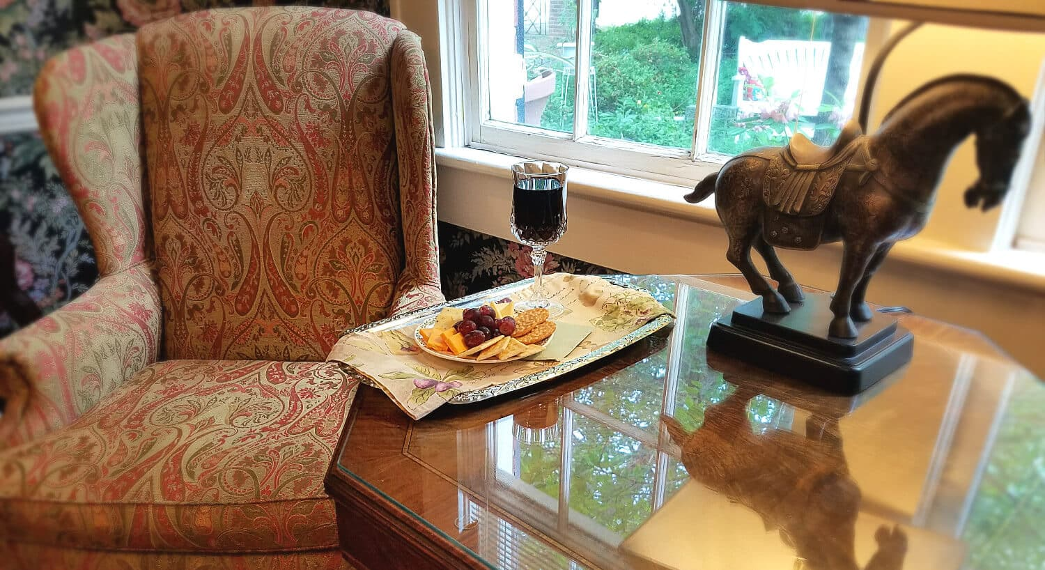 Wine, cheese and crackers on a tray next to an unhostered chair by a window.