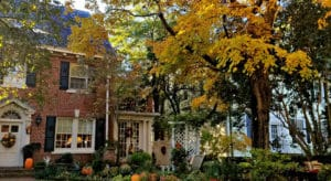 Large brick home in autumn with fall foliage in front.