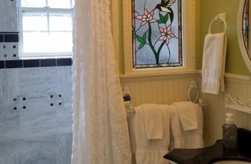Bathroom in white with lace shower curtain and stained glass window.