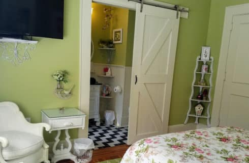 Whimisical bedroom leading to bathroom with a barn-door style door and black and white tile.