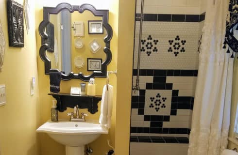 Bathroom decorated in gold and balck with a shower and vanity sink.