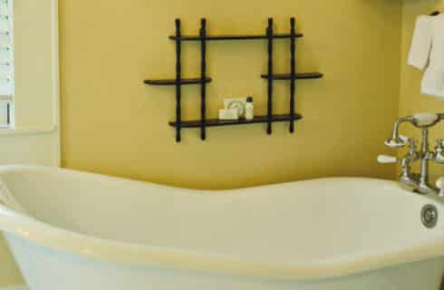 Clawfoot tub in a bathroom painte din gold with black accents.