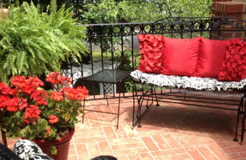 Brick patio seating area with black wrought-iron furniture and red accents.