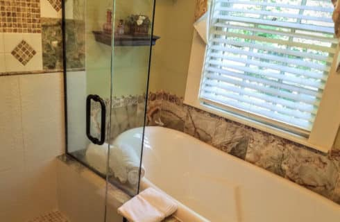 Bathroom with a separate shower and claw-foot tub.