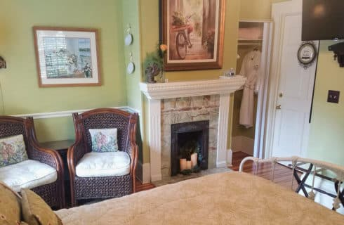 Large and bright guestroom with pale green paint and a fireplace.