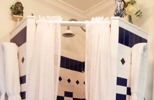 Shower enclosure with unique black and white tile and a white shower curtain.