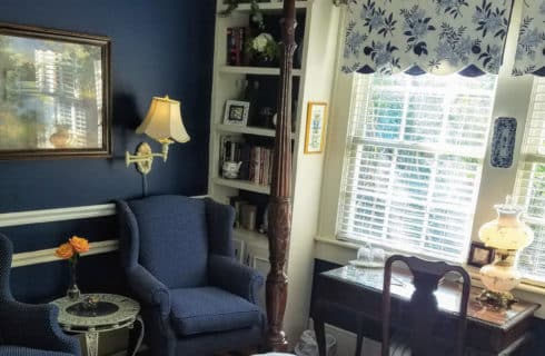 Elegant bedroom decorate din navy blue with white accents and brown furniture.