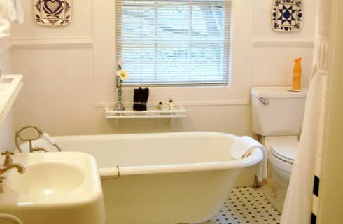 White clawfoot tub in a white bathroom with vanity sink and stool.