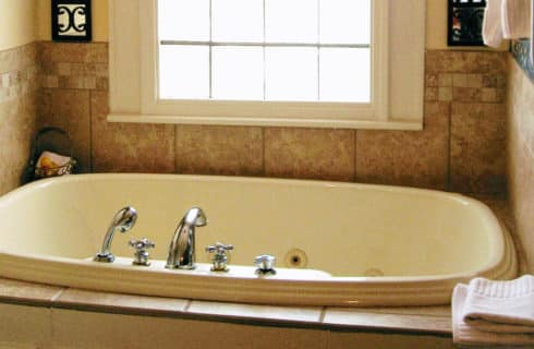 Soaking tubs with jets in tile enclosure under a window.