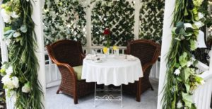 Table for two set outside with ivy background