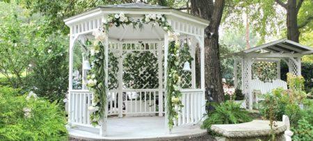 Floral decorated white gazebo and glider in garden.