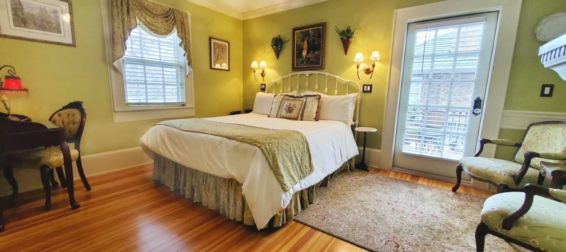 California king bed with two cushioned chairs near balcony door and fireplace.