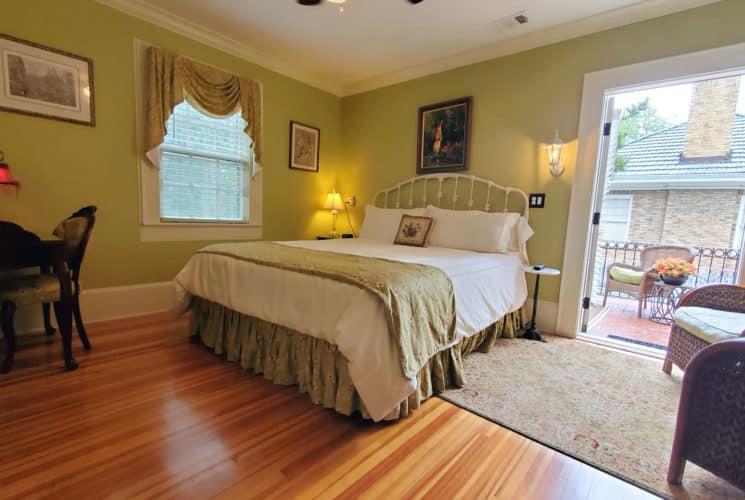 California Bed near antique desk by open balcony door.