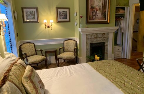Comfortable chairs by antique candlelit fireplace with pictures on wall and small table