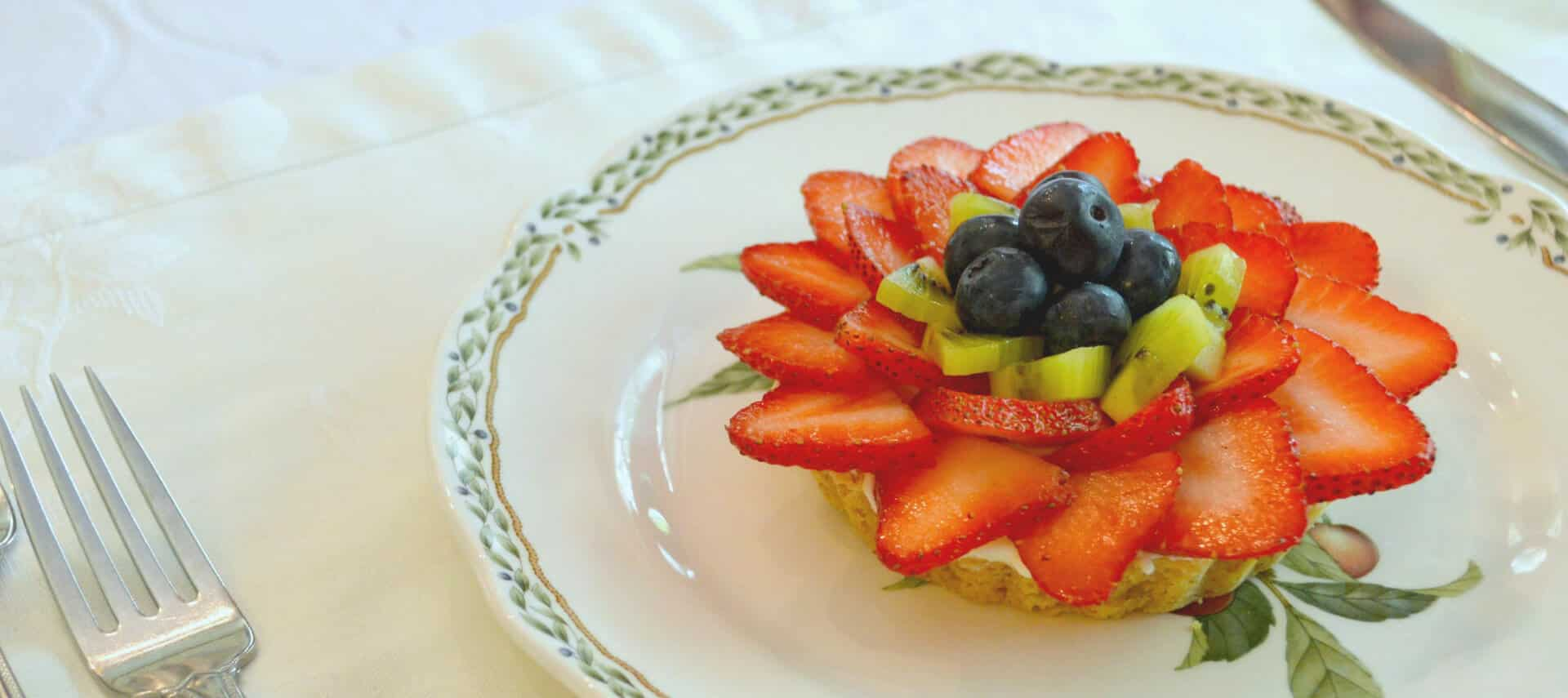 Fruit tart with strawberries, kiwi and blueberries on a china plate.