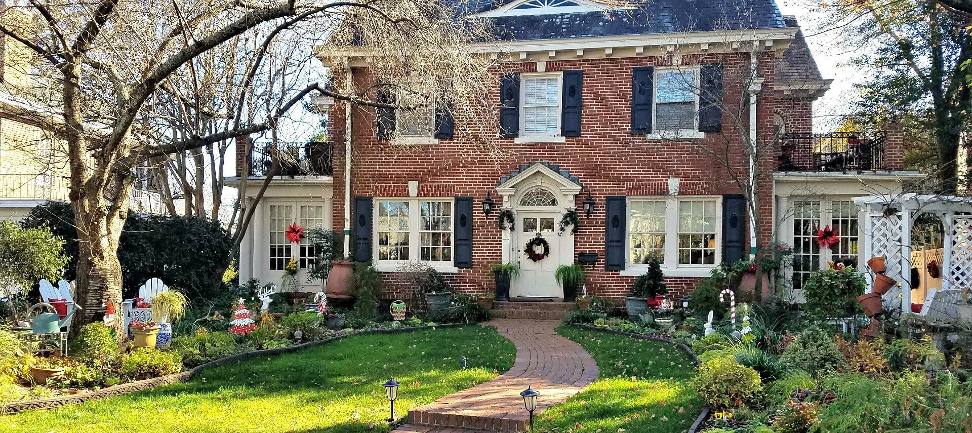 Front brick colonial house with Christmas wreath and decorations scattered around the lawn.