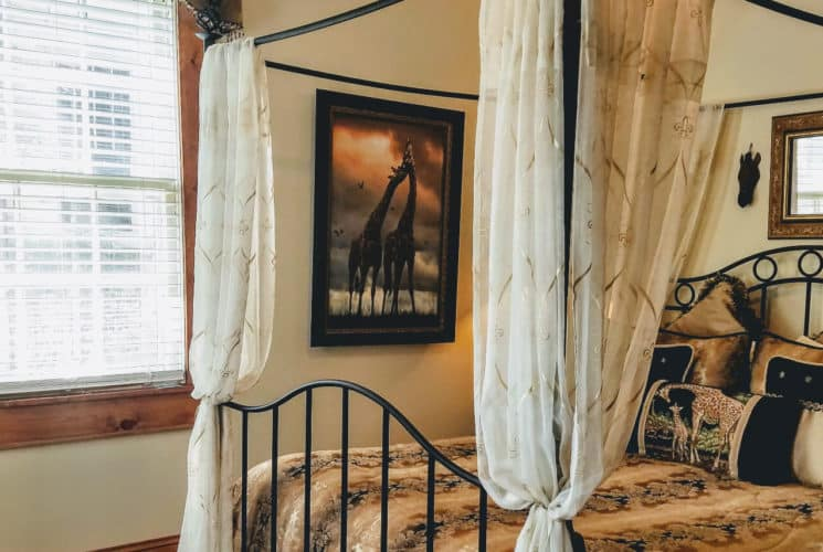 Black iron canopy bedstead with luxurious bedding in black and tan with giraffe accents.