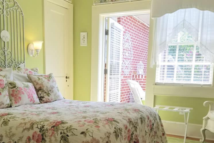 Lovely light-filled bedroom painted pale green with queen bed made up in a pink patterened spread.