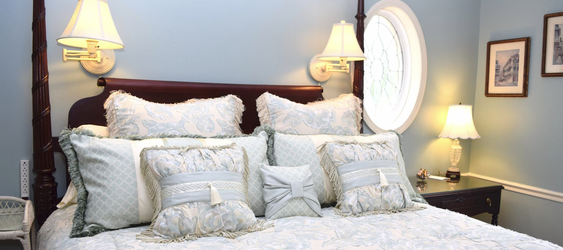 Large four-poster bed made up in white with many decorative pillows.