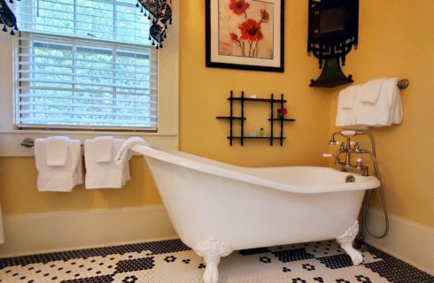 Slipper clawfoot tub in large tiled bathroom