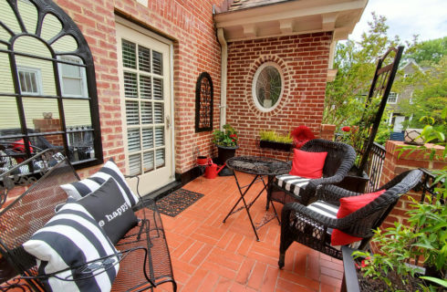 Red brick balcony with black wicker seating and pillows