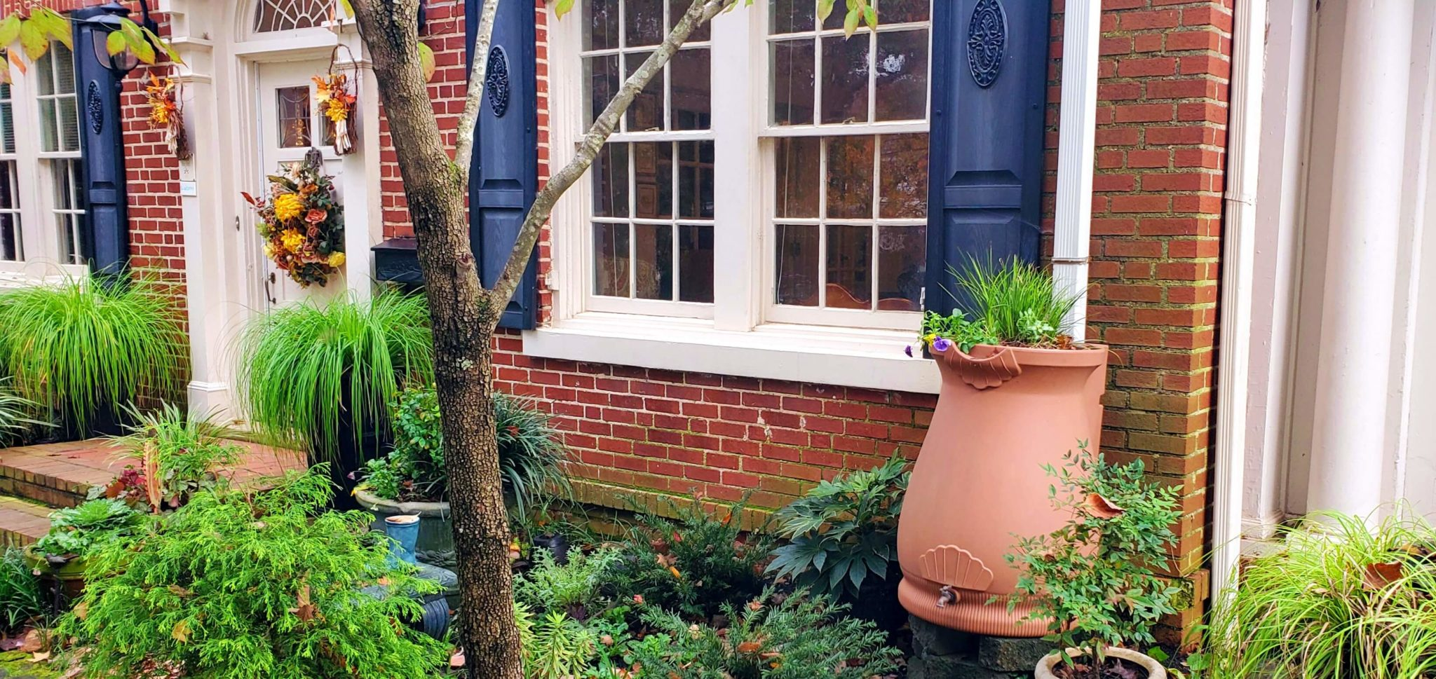 Rain water collection bucket in front of red brick house in garden.