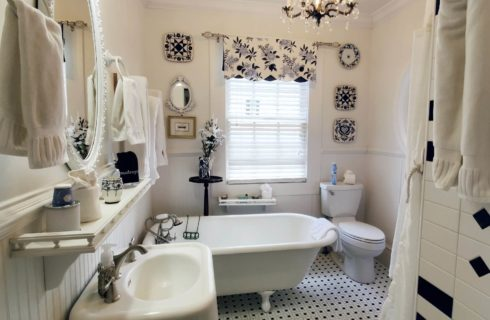 Antique clawfoot tub in large white bathroom with blue accents